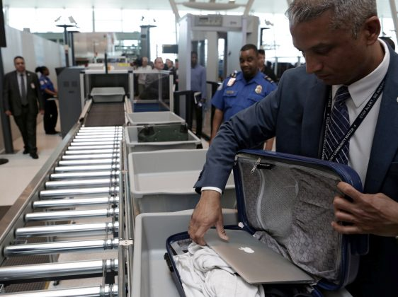 FILE PHOTO: A TSA official removes a laptop from a bag for scanning using the Transport Security Administration's new Automated Screening Lane technology at Terminal 4 of JFK airport in New York City, U.S., May 17, 2017. REUTERS/Joe Penney/File Photo