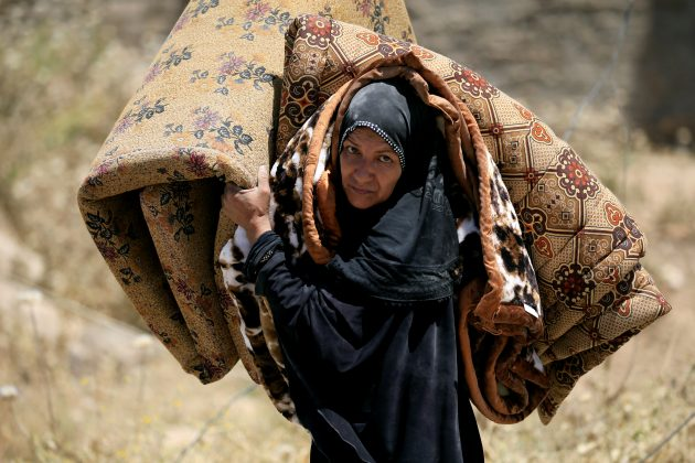 A displaced Iraqi woman who fled her home, carries a mattress in al-Zanjili neighbourhood, north of Old City district of Mosul, Iraq.