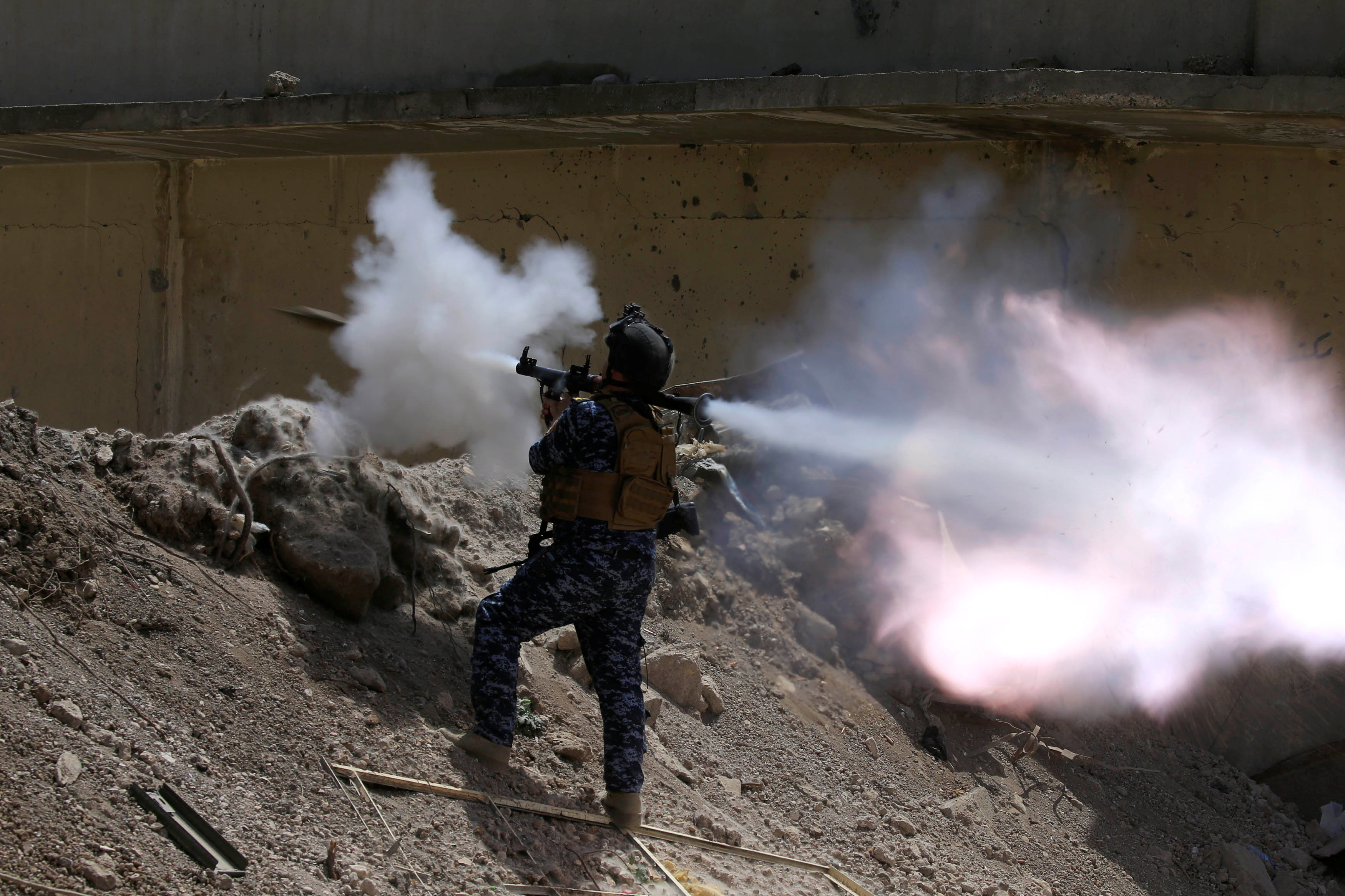 An Iraqi Federal Police member fires an RPG towards Islamic State militants during a battle in western Mosul.