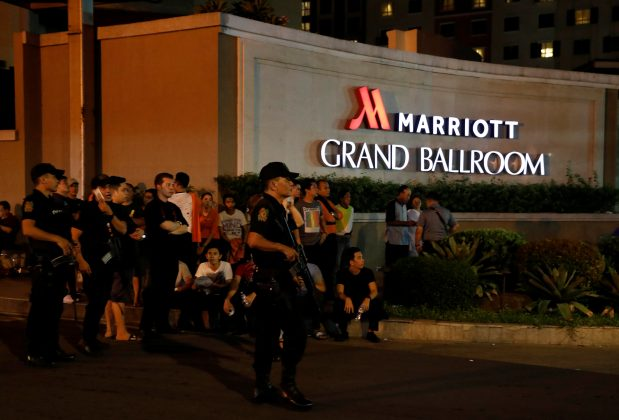Policemen stand guard near evacuated employees of a hotel near a situation at a Resorts World building, in Pasay City, Metro Manila, Philippines June 2, 2017. REUTERS/Erik De Castro
