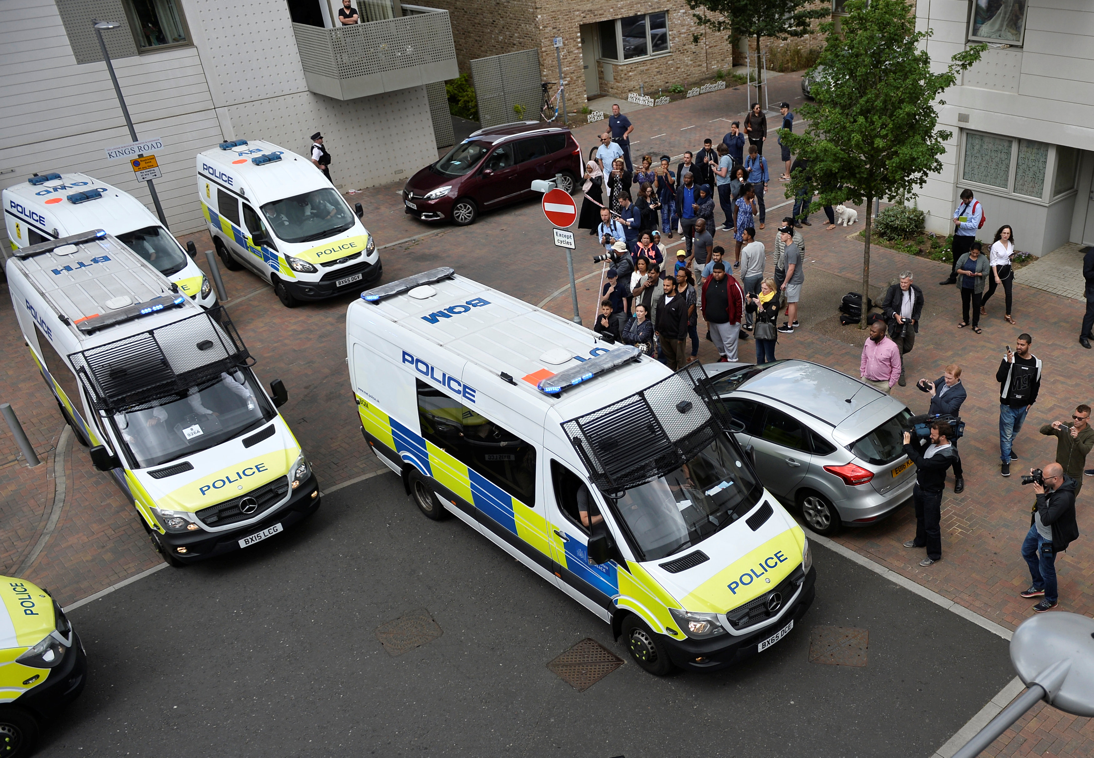 Police vans leave carrying a number of women who were detained after a block of flats was raided in Barking, east London,