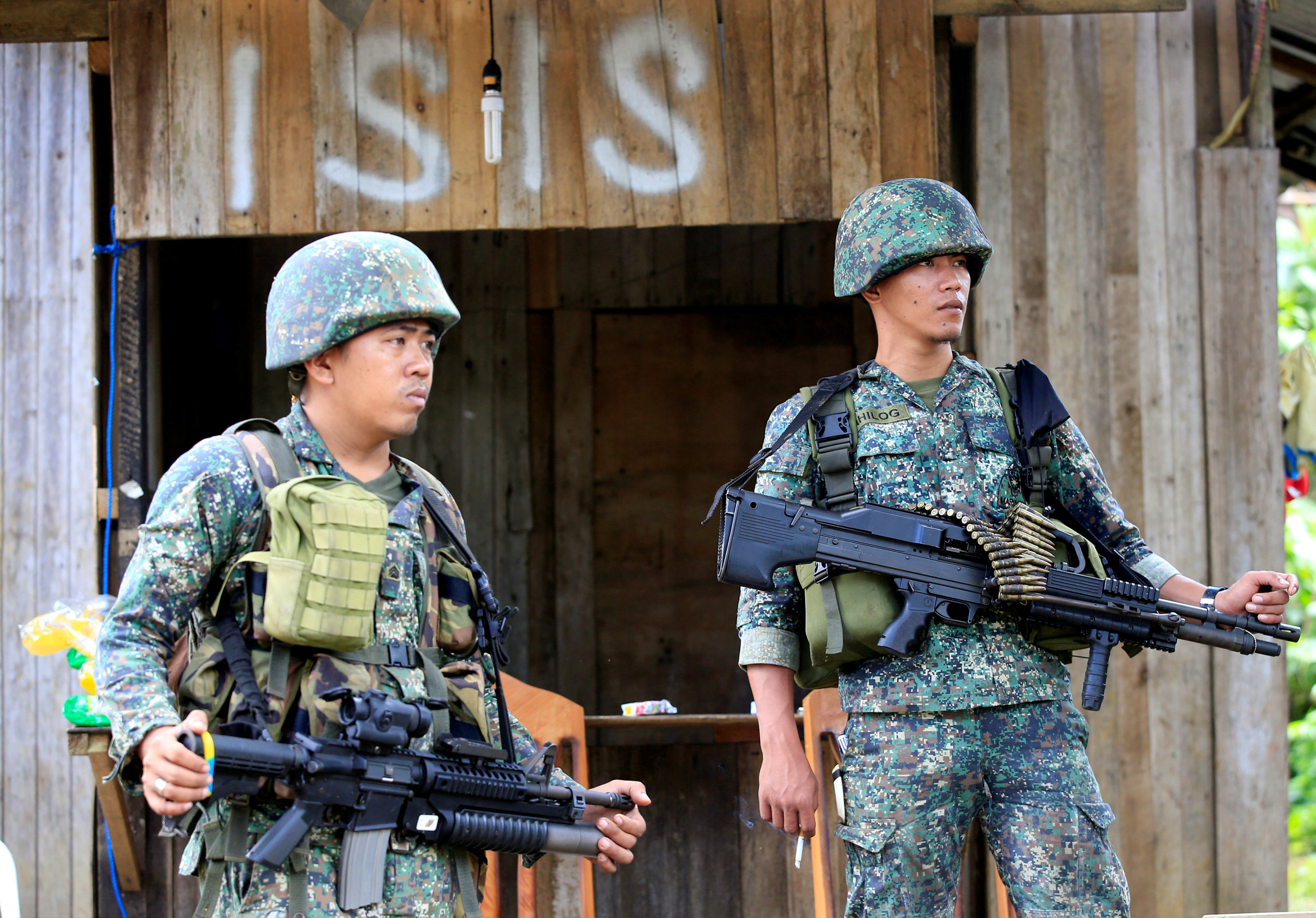Soldiers stand guard along the main street of Mapandi village as government troops continue their assault on insurgents from the Maute group, who have taken over large parts of Marawi City, Philippines June 2,