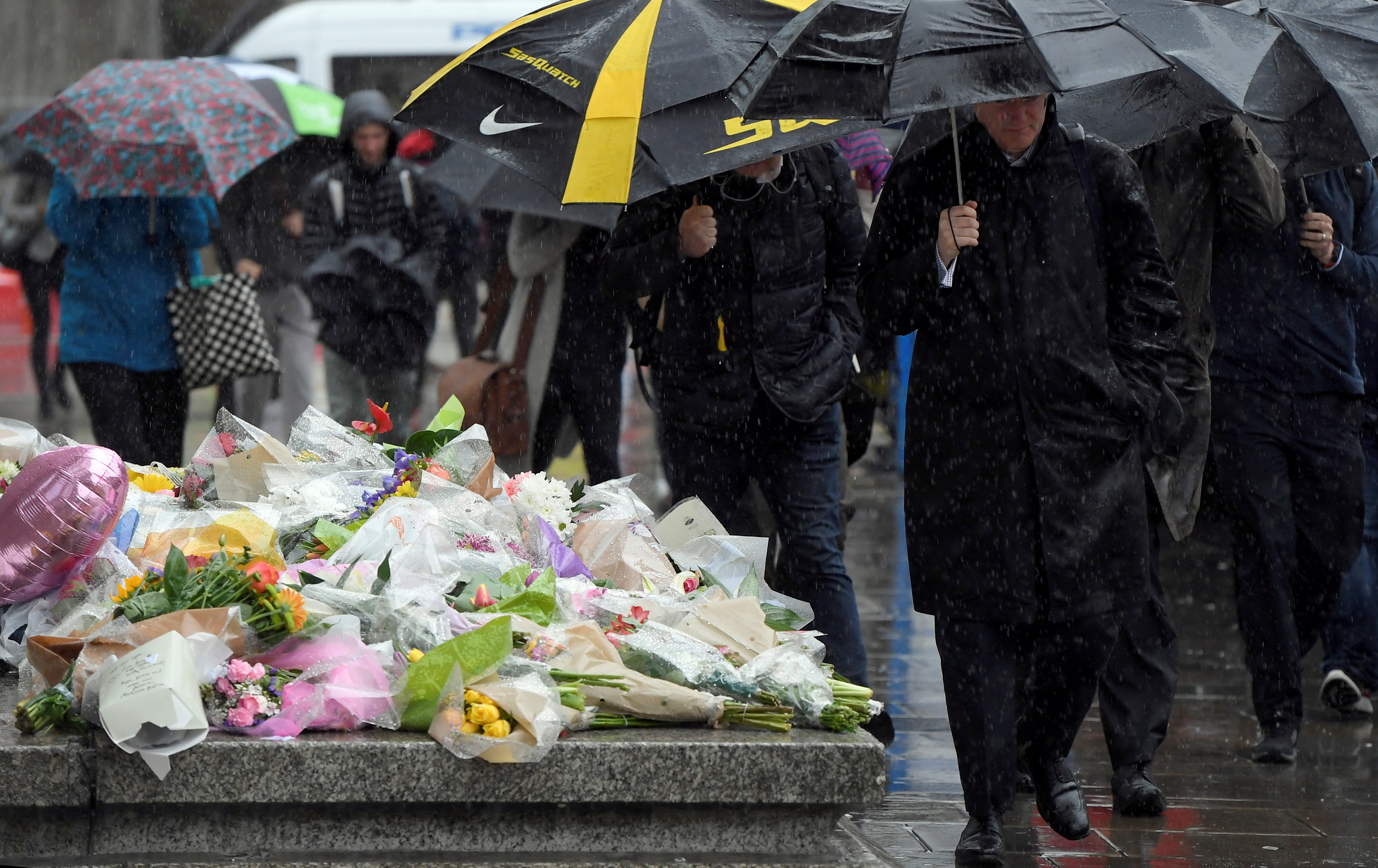 Pedestrians carry umbrellas as they walk past floral tributes to the victims of the recent attack at London Bridge and Borough Market, in central London, Britain June 6, 2017. REUTERS/Toby Melville