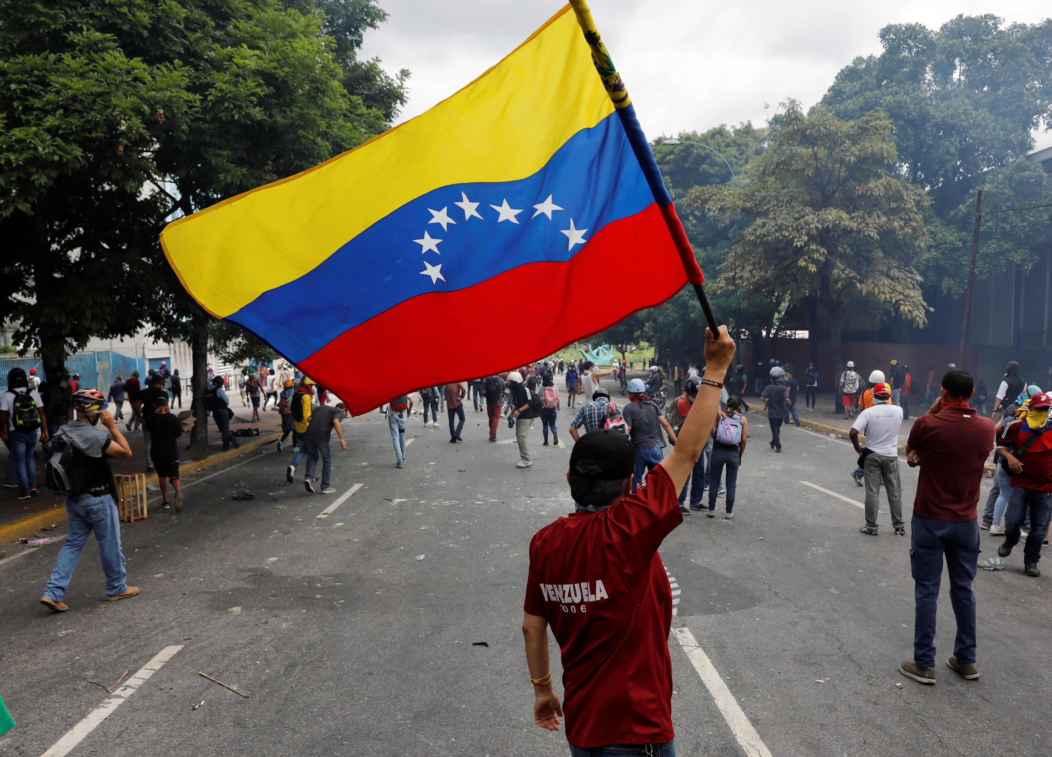 A demonstrator waves a Venezuela's flag while clashing with riot security forces during a rally against Venezuela's President Nicolas Maduro in Caracas, Venezuela June 5, 2017. REUTERS/Carlos Garcia Rawlins