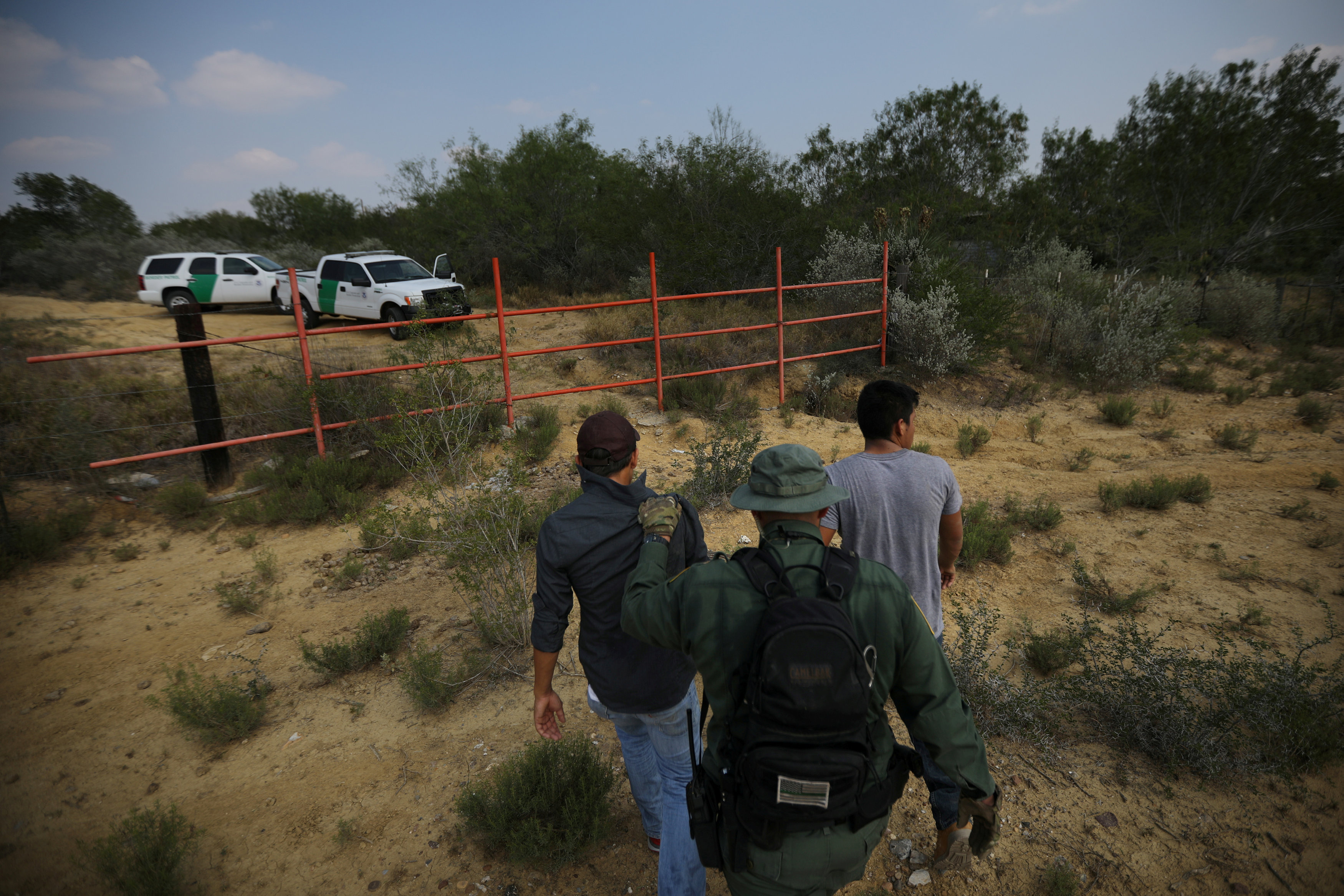FILE PHOTO - A U.S. border patrol agent escorts men being detained after entering the United States by crossing the Rio Grande river from Mexico, in Roma, Texas, U.S. on May 11, 2017. REUTERS/Carlos Barria/File Photo