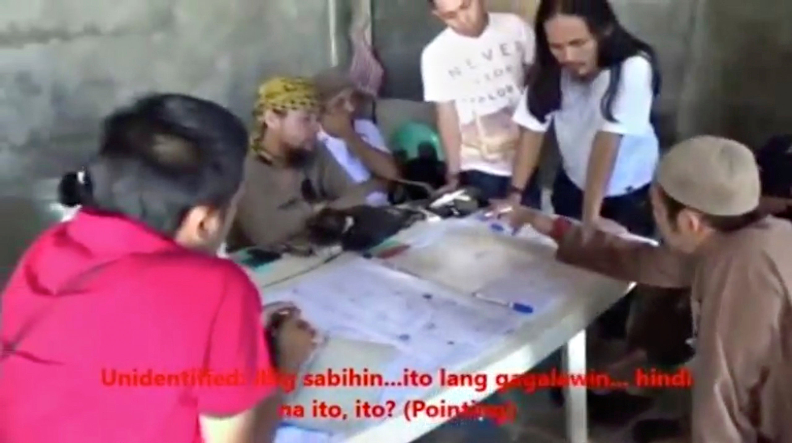 Men identified by Philippines Intelligence officers as Isnilon Hapilon (2nd L, yellow headscarf) and Abdullah Maute (2nd R, standing, long hair) are seen in this still image taken from video released by the Armed Forces of the Philippines on June 7, 2017.