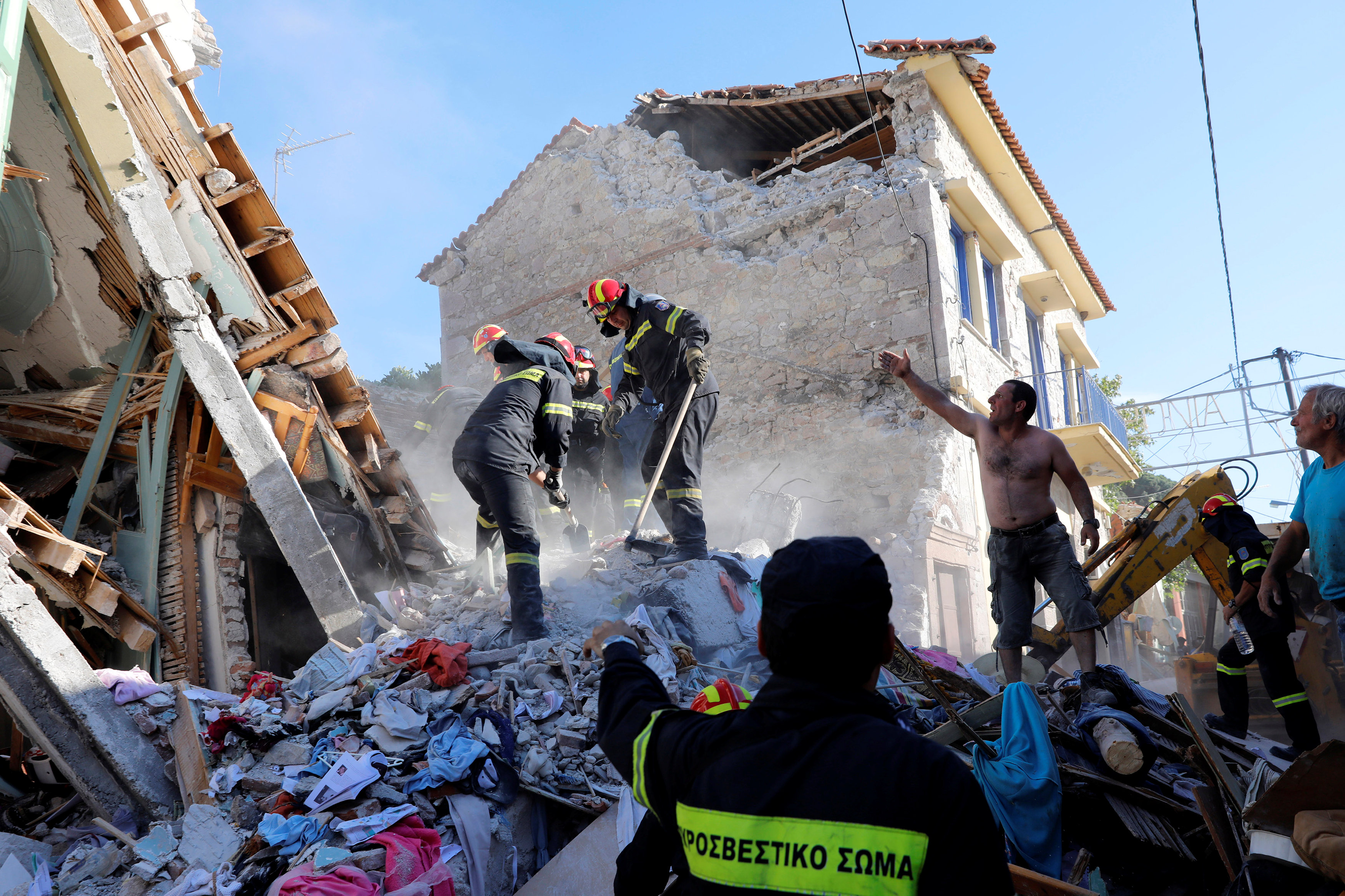 Rescue team members search for victims at a collapsed building in the village of Vrissa on the Greek island of Lesbos, Greece, after a strong earthquake shook the eastern Aegean,