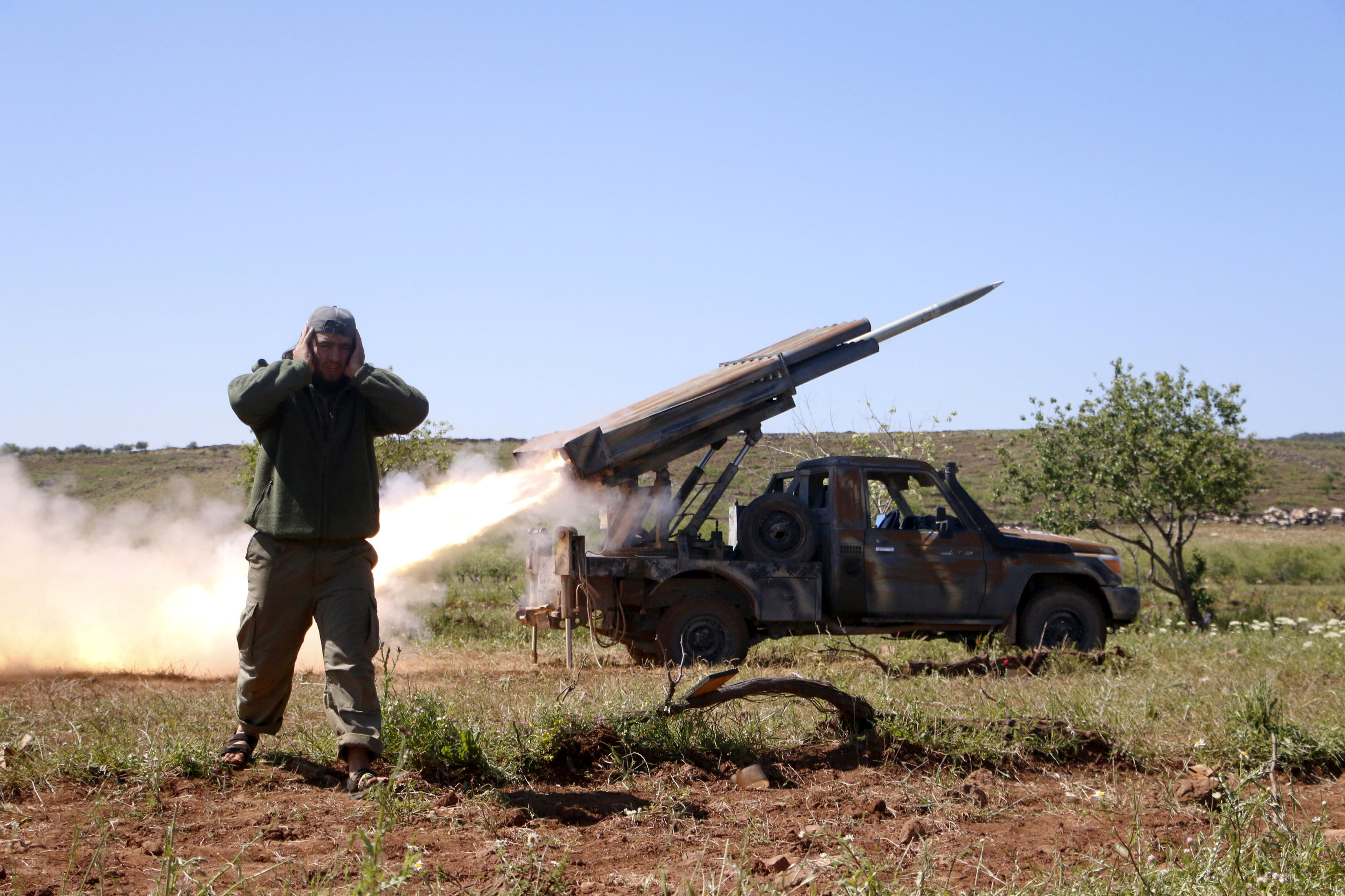 FILE PHOTO: A rebel fighter from the Ahrar al-Sham Islamic Movement reacts as they fire grad rockets from Idlib countryside, towards forces loyal to Syria's President Bashar al-Assad stationed at Jureen town in al-Ghab plain in the Hama countryside, Syria, April 25, 2015. REUTERS/Mohamad Bayoush/File Photo