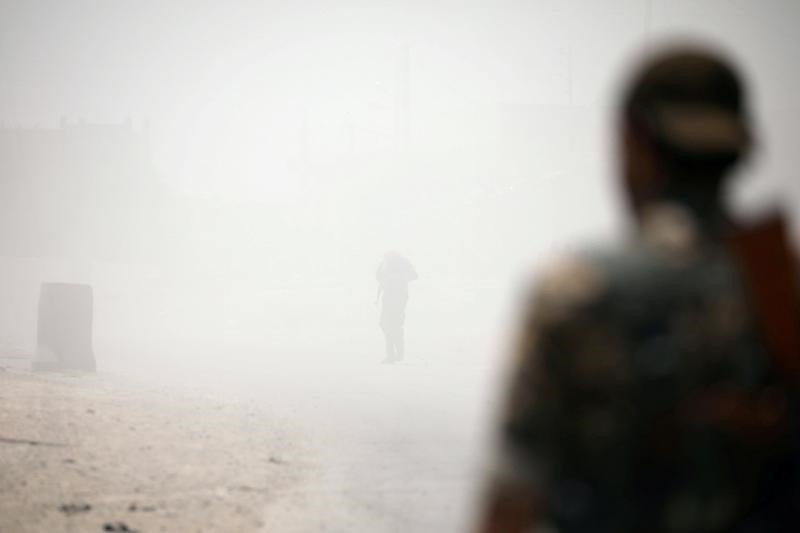 "FILE PHOTO"" Syrian Democratic Forces (SDF) fighters stand amid smoke in Raqqa's western neighbourhood of Jazra, Syria June 11, 2017. REUTERS/Rodi Said"