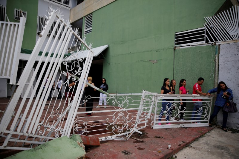 People walk past the broken fencing of a building after opposition supporters and security forces clashed in and outside the building on Tuesday according to residents, in Caracas, Venezuela June 14, 2017. REUTERS/Ivan Alvarado