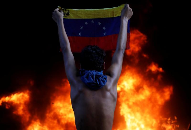FILE PHOTO - A protester holds a national flag as a bank branch, housed in the magistracy of the Supreme Court of Justice, burns during a rally against Venezuela's President Nicolas Maduro, in Caracas, Venezuela June 12, 2017. REUTERS/Carlos Garcia Rawlins
