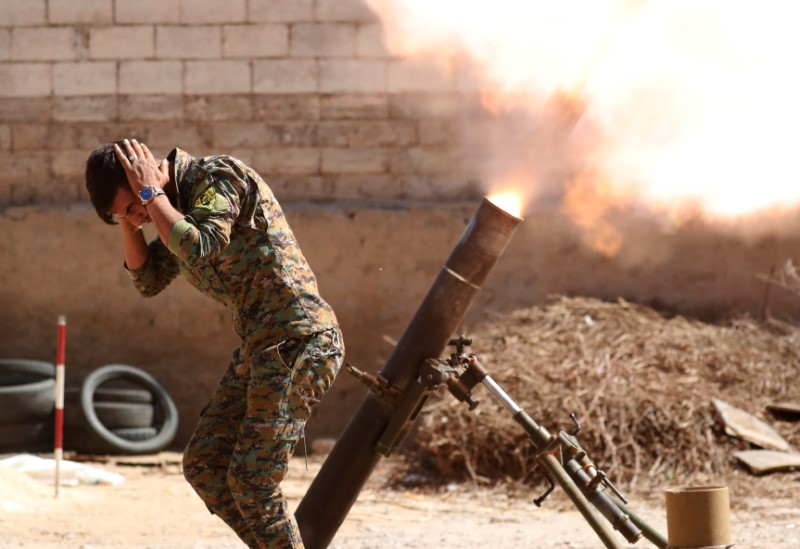 A Kurdish fighter from the People's Protection Units (YPG) fires a 120 mm mortar round in Raqqa, Syria, June 15, 2017. REUTERS/Goran Tomasevic