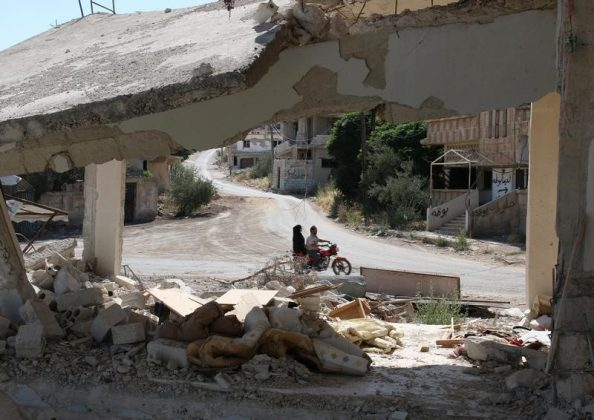 People ride a motorbike past a damaged building in a rebel-held part of the southern city of Deraa, Syria, June 15, 2017. REUTERS/Alaa Al-Faqir