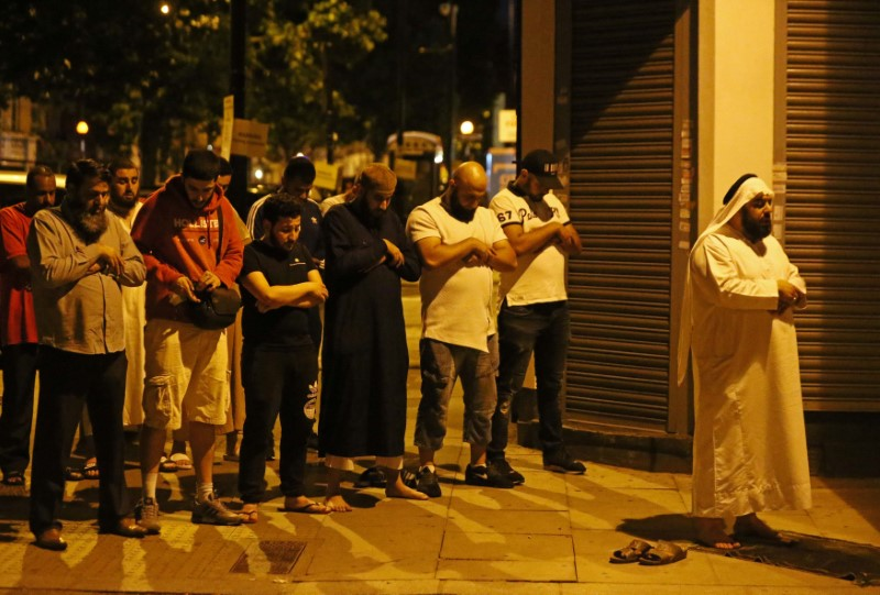 Men pray after a vehicle collided with pedestrians near a mosque in the Finsbury Park neighborhood of North London, Britain June 19, 2017.