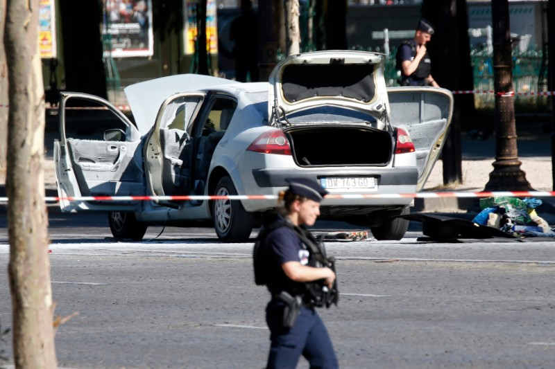 Police secure the area near a burned car at the scene of an incident in which it rammed a gendarmerie van on the Champs-Elysees Avenue in Paris, France, June 19, 2017. REUTERS/Charles Platiau