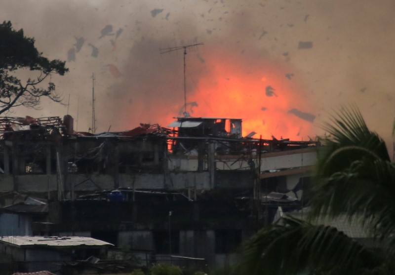 Debris and fire is seen after an OV-10 Bronco aircraft released a bomb, during an airstrike, as government forces continue their assault against insurgents from the Maute group, who have taken over large parts of Marawi City, Philippines June 19, 2017. REUTERS/Romeo Ranoco