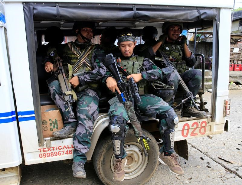 Members of the Philippine National Police (PNP) Special Action Force are onboard a PNP vehicle as reinforcements, as government forces continue their assault against insurgents from the Maute group, who have taken over large parts of Marawi City, Philippines June 19, 2017. REUTERS/Romeo Ranoco
