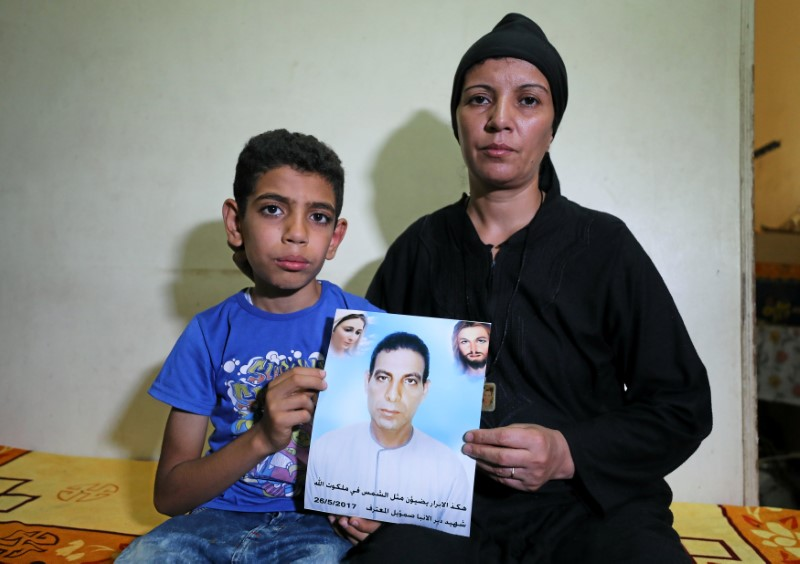 Hanaa Youssef and Mina Habib, the widow and son of a man who was killed in a militant attack against Coptic Christians last month, hold the victim's portrait in Minya, Egypt June 8, 2017. Picture taken June 8, 2017. REUTERS/Mohamed Abd El Ghany