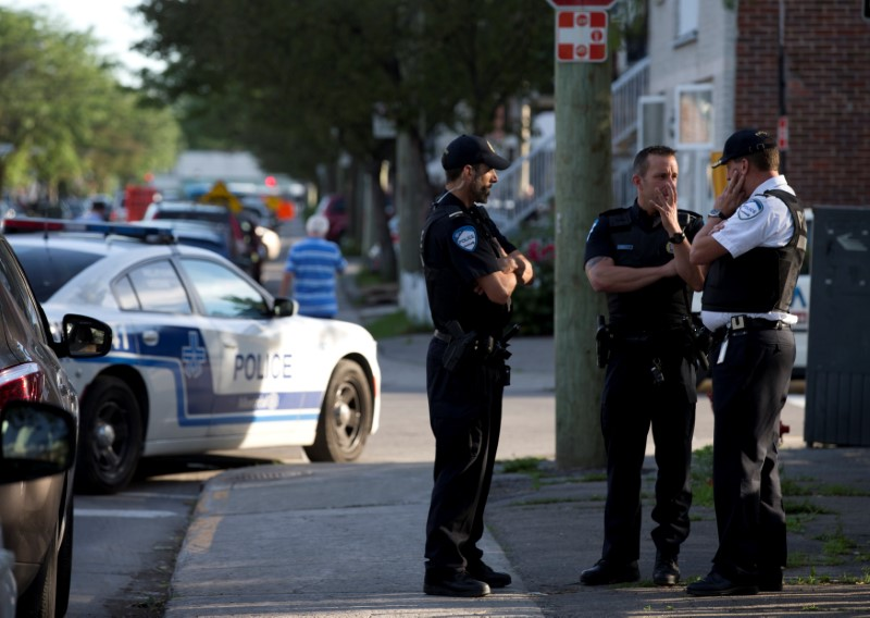 Police investigators talk outside the home of Amor Ftouhi, in Montreal, Quebec, Canada, June 21, 2017. Ftouhi has been identified as a suspect by the FBI in the stabbing of a police officer inside the main terminal of a small airport in Flint, Michigan. REUTERS/Christinne Muschi