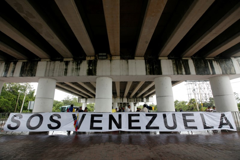 A banner is seen with a small group of Venezuelan protesters outside the site where the Organization of American States (OAS) 47th General Assembly is taking place in Cancun, Mexico June 21, 2017. REUTERS/Carlos Jasso