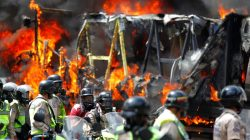 Riot security forces members congregate next to a government truck that was set on fire during a rally against Venezuelan President Nicolas Maduro's government in Caracas, Venezuela June 22, 2017. REUTERS/Christian Veron
