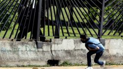 A member of the riot security forces points a gun through the fence of an air force base at David Jose Vallenilla, who was fatally injured during clashes at a rally against Venezuelan President Nicolas Maduro's government in Caracas, Venezuela, June 22, 2017. REUTERS/Carlos Garcia Rawlins/File photo