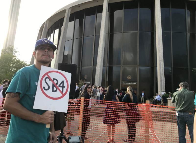 "A protester against the Texas state law to punish ""sanctuary cities"" stands outside the U.S. Federal court in San Antonio, Texas,"