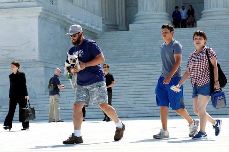People walk outside the the U.S. Supreme Court building after the Court granted parts of the Trump administration's emergency request to put his travel ban into effect immediately while the legal battle continues, in Washington, U.S., June 26, 2017