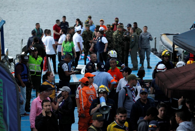 Rescuers wait at the dock after a tourist boat sank with 150 passengers onboard at the Guatape reservoir, Colombia, June 25, 2017