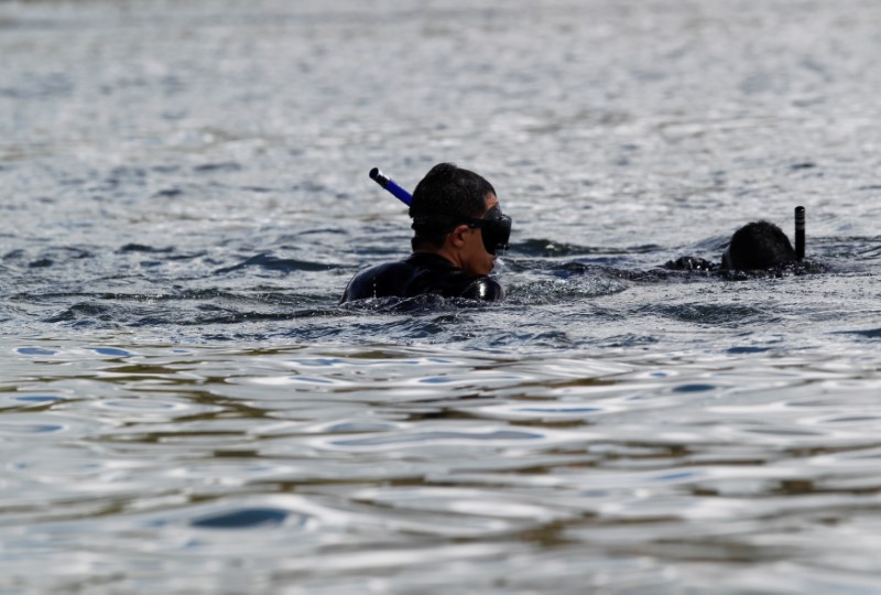 Divers look for people believed to be missing after a tourist boat sank on Sunday in the Penol-Guatape reservoir, in Guatape, Colombia June 26, 2017