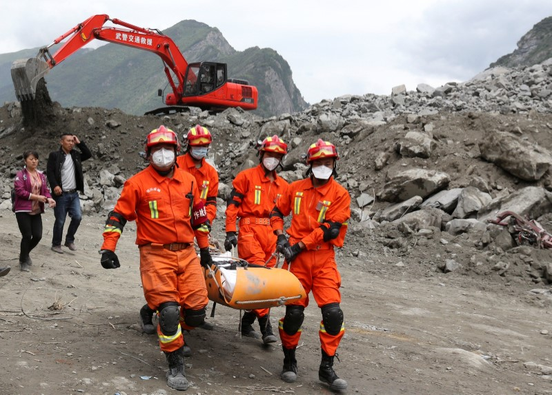 Rescue workers carry a victim at the site of a landslide that occurred in Xinmo Village, Mao County, Sichuan province, China, June 25, 2017.