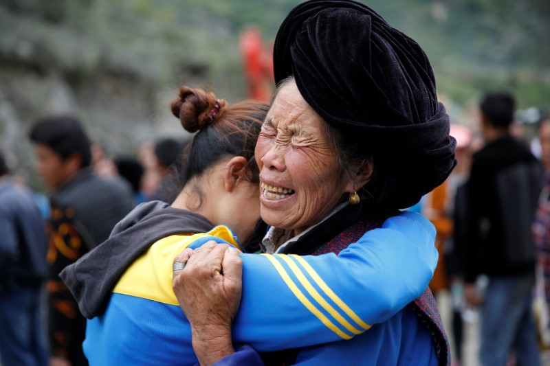 Relatives of victims react at the site of a landslide in the village of Xinmo, Mao County, Sichuan Province, China June 26, 2017.