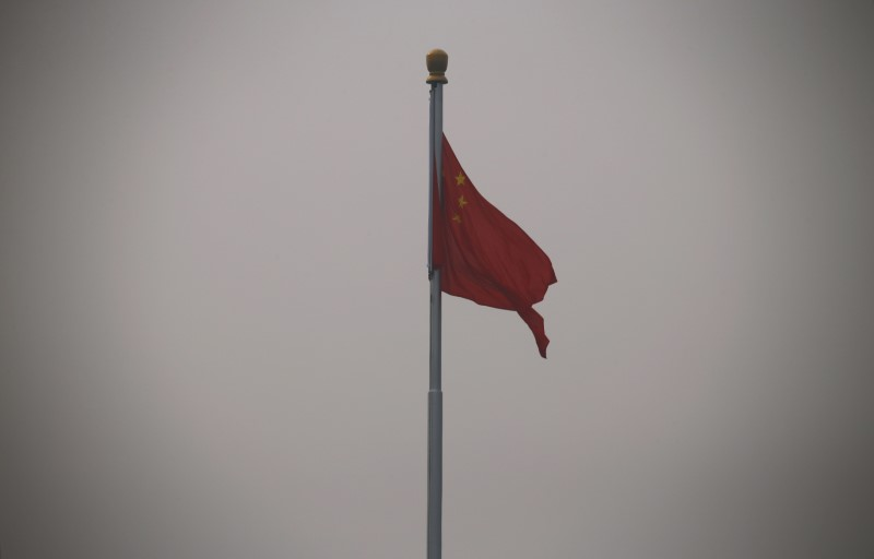 FILE PHOTO: A Chinese national flag flutters at Tiananmen Square in Beijing October 20, 2014. REUTERS/Petar Kujundzic