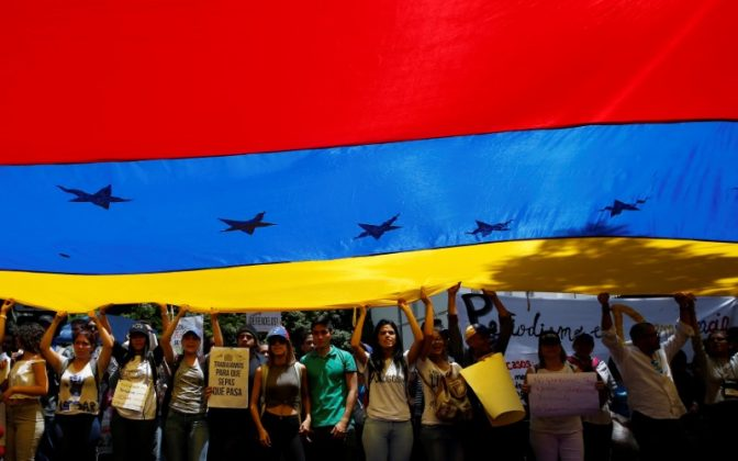 Demonstrators holding a Venezuelan flag attend a rally against Venezuela's President Nicolas Maduro's government in Caracas, Venezuela June 27, 2017. REUTERS/Ivan Alvarado