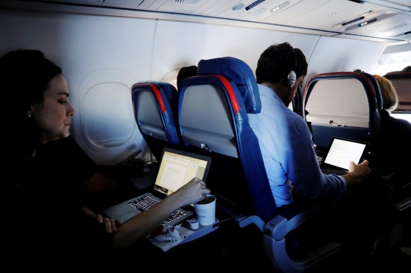 FILE PHOTO -- Passengers use their laptops on a flight out of John F. Kennedy (JFK) International Airport in New York, U.S., May 26, 2017. Picture taken May 26, 2017. REUTERS/Lucas Jackson/File Photo