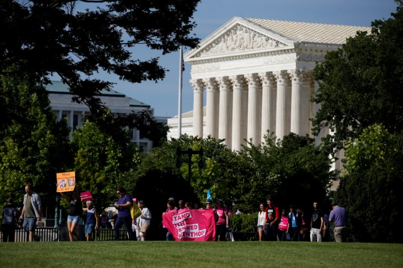 FILE PHOTO: Healthcare activists with Planned Parenthood and the Center for American Progress pass by the Supreme Court as they protest in opposition to the Senate Republican healthcare bill on Capitol Hill in Washington, U.S., June 28, 2017. REUTERS/Joshua Roberts/File Photo
