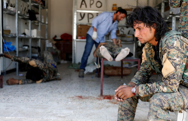 A Syrian Democratic Forces (SDF) fighter sit as medics treat his comrades injured by sniper fired by Islamic State militants in a field hospital in Raqqa, Syria June 28, 2017. REUTERS/Goran Tomasevic