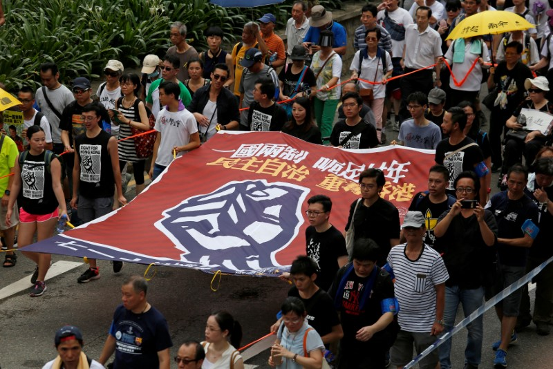 "Pro-democracy protesters carry a banner which reads ""One Country, Two Systems, a cheating for twenty years. Recapture Hong Kong with democracy and self-determination"", during a demonstration on the 20th anniversary of the territory's handover from Britain to Chinese rule, in Hong Kong, China July 1, 2017. REUTERS/Bobby Yip"
