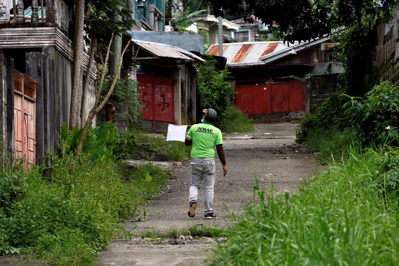 A member of a humanitarian volunteers team walks with a white flag as he searches for survirvors or victims due to the fighting in the center of Marawi City, Philippines J
