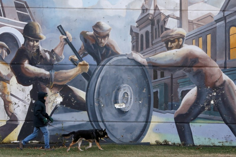 A man walks his dog past a mural depicting factory workers in the historic Pullman neighborhood in Chicago