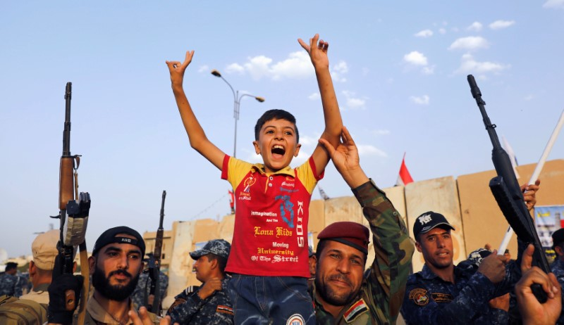 Members of Iraqi Federal Police carry a boy as they celebrate victory of military operations against the Islamic State militants in West Mosul, Iraq July 2, 2017.