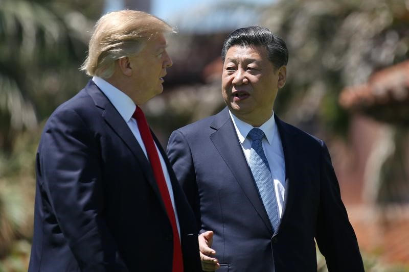 U.S. President Donald Trump and China's President Xi Jinping chat as they walk along the front patio of the Mar-a-Lago estate after a bilateral meeting in Palm Beach, Florida, U.S., April 7,