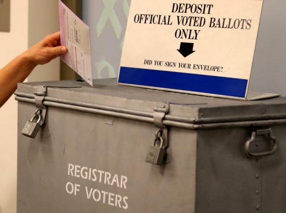 FILE PHOTO: A ballot is placed into a locked ballot box by a poll worker as people line-up to vote early at the San Diego County Elections Office in San Diego, California, U.S., November 7, 2016. REUTERS/Mike Blake/File Photo