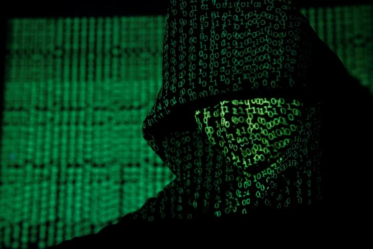 FILE PHOTO - A projection of cyber code on a hooded man is pictured in this illustration picture taken on May 13, 2017. REUTERS/Kacper Pempel/Illustration