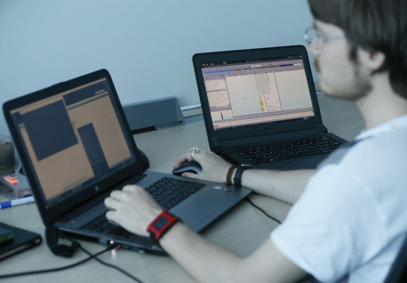 A view shows a laptop display (R) showing part of a code, which is the component of Petya malware computer virus according to representatives of Ukrainian cyber security firm ISSP, with an employee working nearby at the firm's office in Kiev, Ukraine July 4, 2017. REUTERS/Valentyn Ogirenko