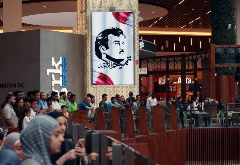 A painting depicting Qatar's Emir Sheikh Tamim Bin Hamad Al-Thani is seen as people gather to watch players from Spain's national team in Mall of Qatar in Doha, Qatar July 5, 2017. Picture taken July 5, 2017. REUTERS/Naseem Zeitoon