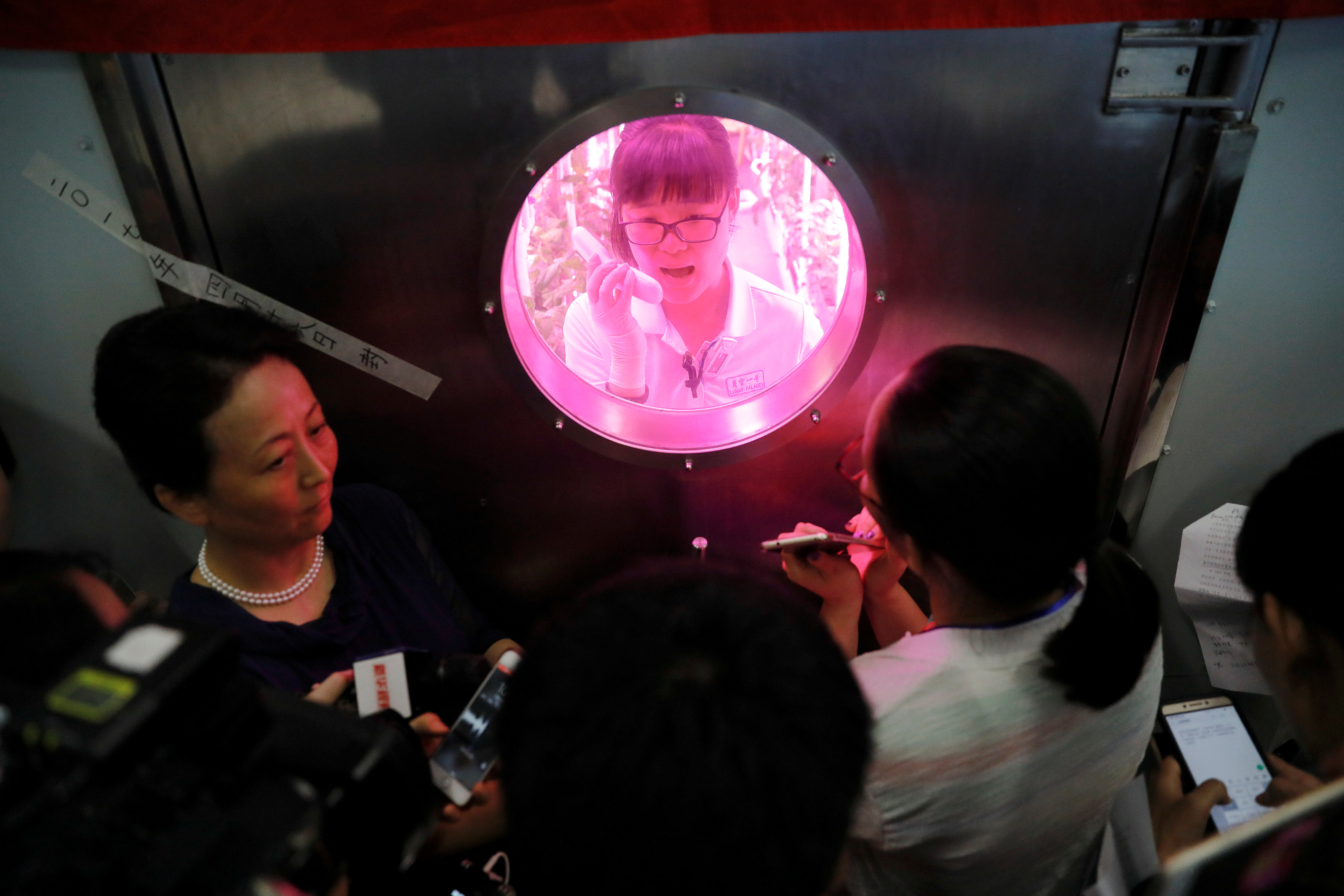 A volunteer answers reporters' questions from inside a simulated space cabin in which she temporarily lives with others as a part of the scientistic Lunar Palace 365 Project, at Beihang University in Beijing, China