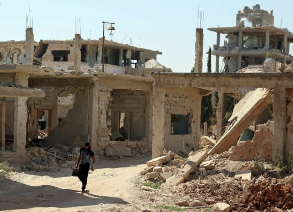 A Free Syrian Army fighter carries a weapon as he walks past damaged buildings in a rebel-held part of the southern city of Deraa, Syria July 9, 2017. REUTERS/Alaa Al-Faqir