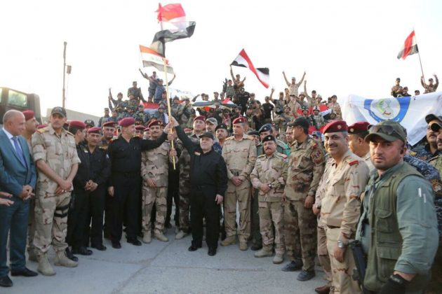 Iraqi Prime Minister Haider al-Abadi (C) holds an Iraqi flag as he announces victory over Islamic State in Mosul, Iraq, July 10, 2017. Iraqi Prime Minister Media Office/Handout via REUTERS