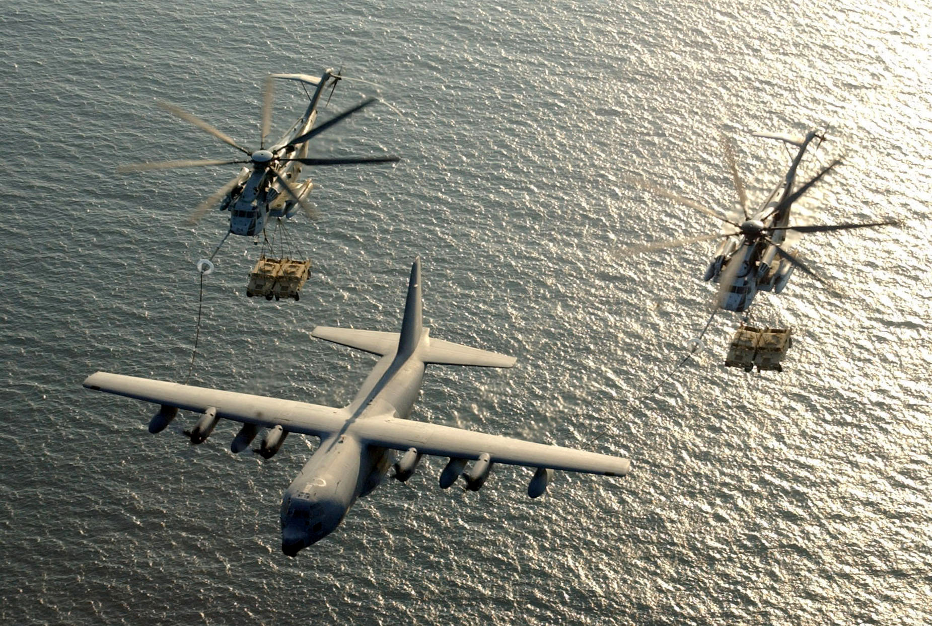 FILE PHOTO: Two U.S. Marine Corps CH-53E Super Stallion helicopters receive fuel from a KC-130 Hercules over the Gulf of Aden January 1, 2003. U.S. Marine Corps/Cpl. Paula M. Fitzgerald/Handout/File Photo via REUTERS